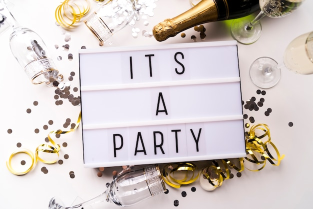White light box with it's a party text and champagne bottle over white backdrop