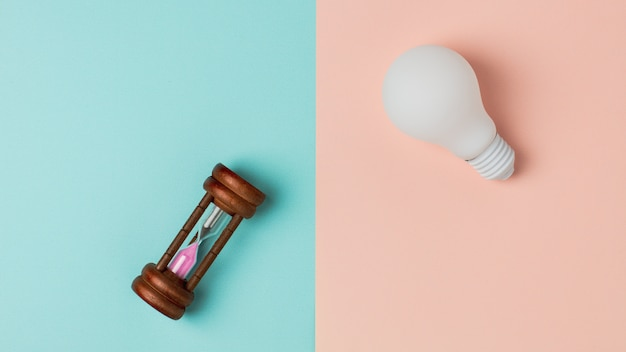 White light bulb and a old hourglass on blue and pink background