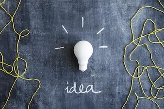 書かれたアイデアテキストとウールスレッドの白い電球