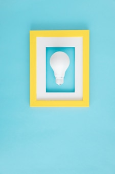 White light bulb with yellow and white border frame over the blue background