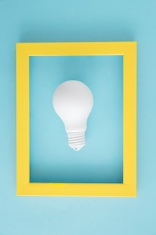 White light bulb with yellow frame on blue backdrop