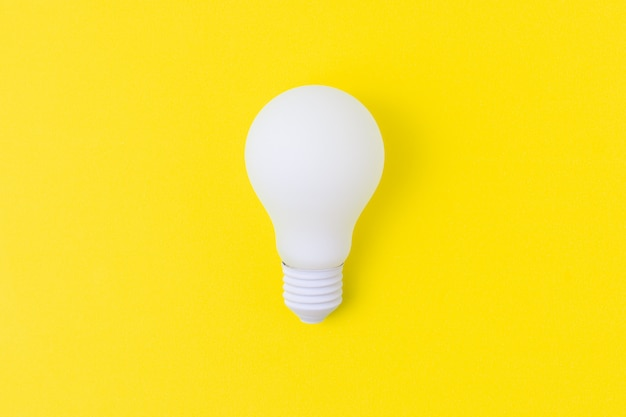 White light bulb on yellow background