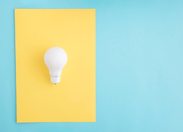 White light bulb on yellow paper over the blue background