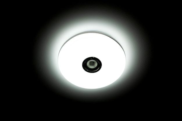 검정색 배경 위에 무선 스피커가 내장된 백색광 led 천장 조명.