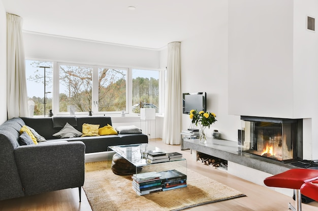 White light living room with l shaped couch with colorful cushions and fireplace with granite shelf against window