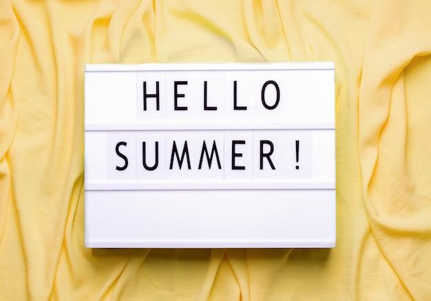 Белый лайтбокс со словами привет лето на желтом пространстве
