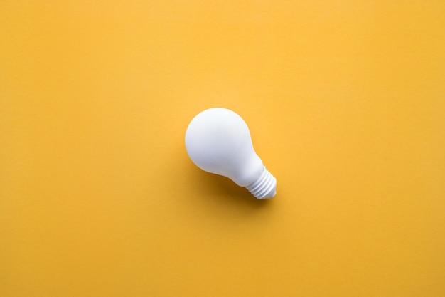 파스텔 색상 배경에 흰색 전구입니다. 아이디어 창의성, 영감, 개념입니다. 평면 디자인입니다.