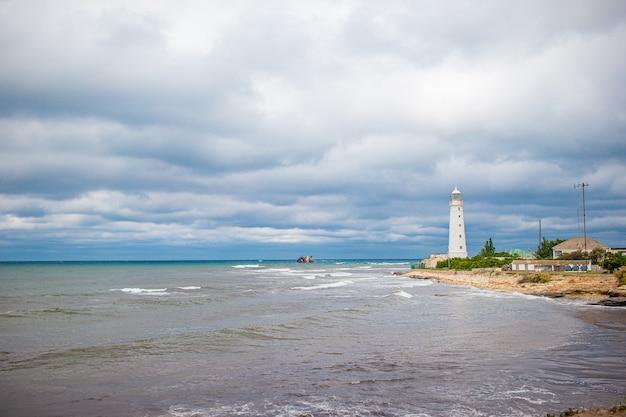 Белый маяк в бухте на море