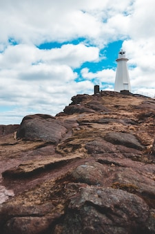 White lighthouse on mountain cliff under cloudy sky during daytime