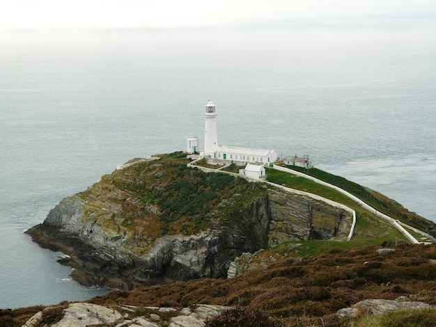 육지 가장자리에 있는 흰색 등대와 웨일즈 배경에 잔잔한 바다