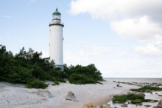 Белый маяк в окружении деревьев у берега пляжа с облачным небом