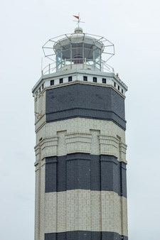 空を背景に夏の日に黒い縞模様の白い灯台