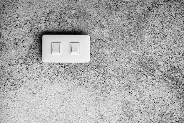 White lighting switch at concrete wall.