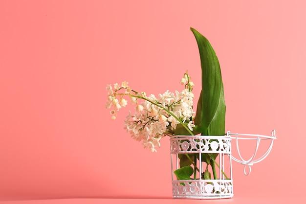 Белая сирень и ландыши в железной клетке для птиц на розовом фоне