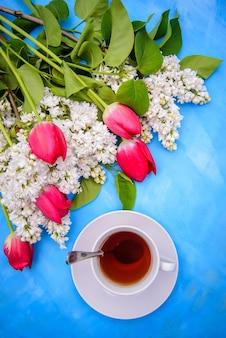 Белые сиреневые и красные тюльпаны и чай на синем фоне для дизайна открытки, упаковки и обложки