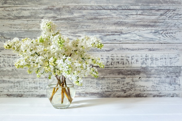 White lilac bouquet in glass vase on wooden table. spring branches of blooming lilac festive bouquet of flowers with copy space.