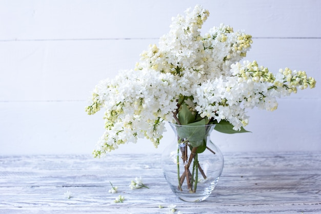 White lilac bouquet in glass vase on wooden table spring branches of blooming lilac festive bouquet