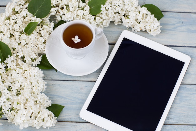 White lilac, a tablet and a cup of tea