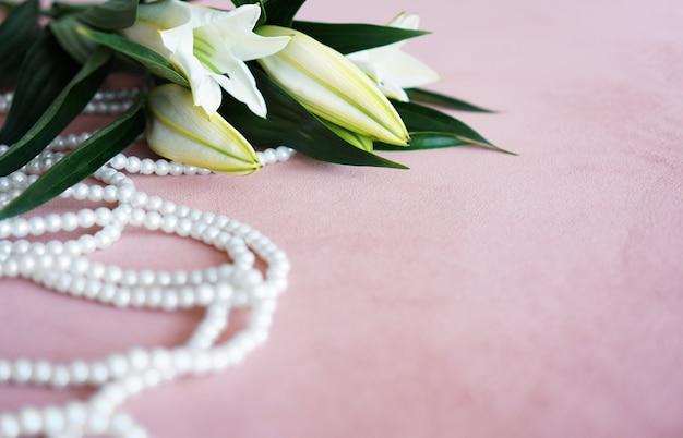 Белые лилии с зелеными листьями и ожерелье из жемчуга на розовом фоне. нежный фон с местом для текста.
