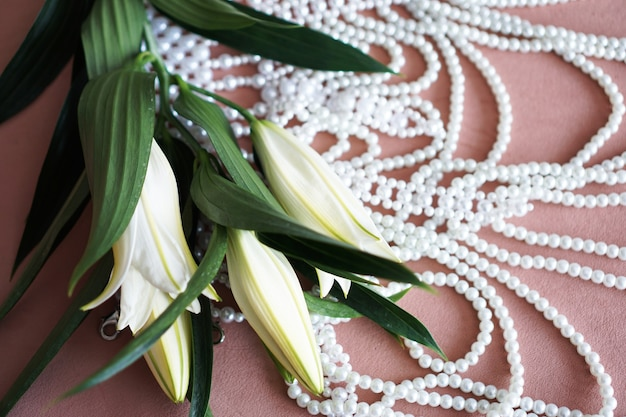 Белые лилии с зелеными листьями и ожерелье из жемчуга на розовом фоне. выборочный фокус