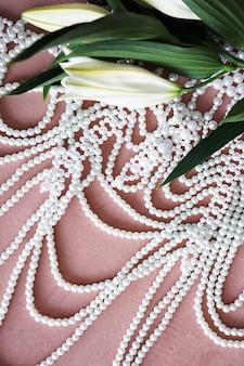 Белые лилии с зелеными листьями и ожерелье из жемчуга на розовом фоне.