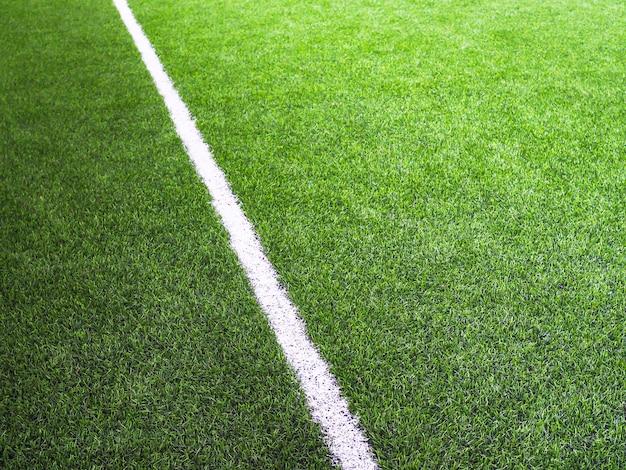 Белая линия на зеленой траве поля для мини-футбола или футбольного поля