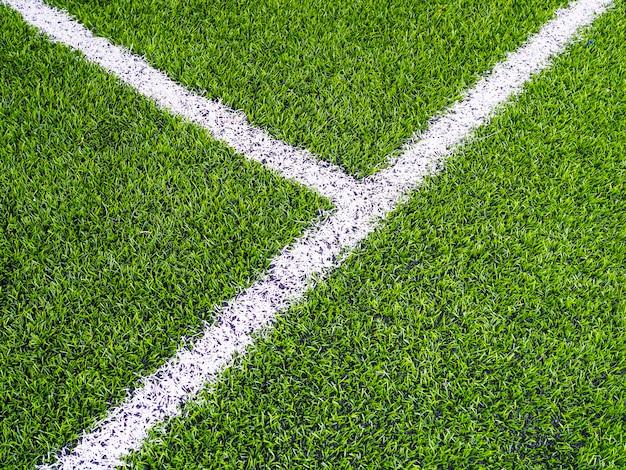 Белая линия на зеленой траве на футбольном поле или поле для мини-футбола.