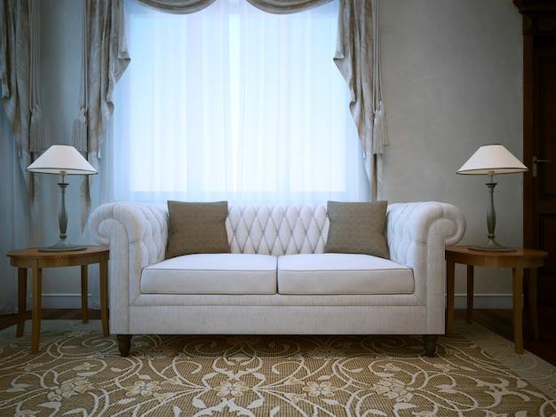 両側のテーブルにランプが付いた白いリネンの綿のソファ。