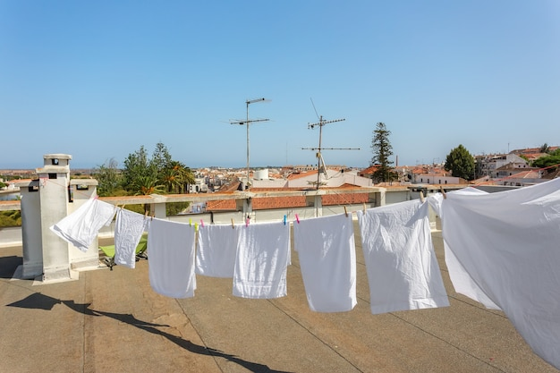 Белое белье, развешанное на крыше балкона для просушки.