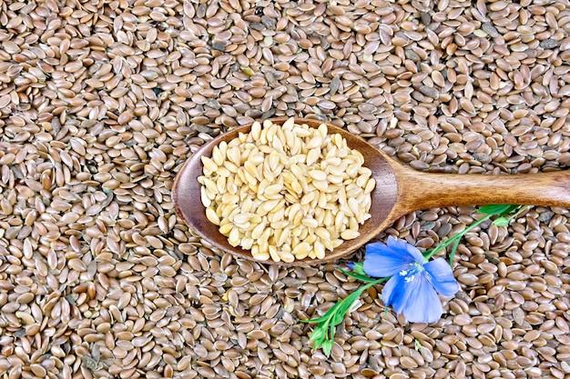 木のスプーンで白いリネンの種子、茶色の亜麻仁を背景に青い亜麻の花