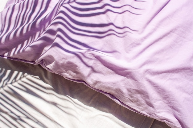 White linens and lavender pillows. natural textiles. trend contrasting shadows with palm leaves