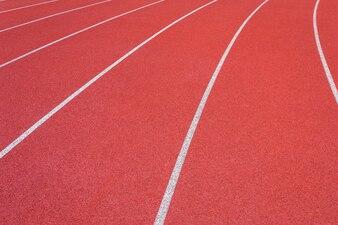 スタジアムの白い線と野外の競馬場レッドゴム競技場の質感