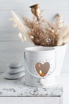 Белая горящая свеча аромата и золотые сухие цветы на деревенском столе. открытка на свадьбу или торжество в монохромном стиле