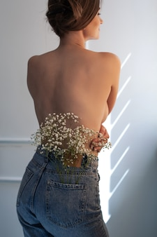 청바지 뒷주머니에 흰색 작은 꽃을 입고 아름 다운 건강 한 벌 거 벗은 등을 가진 여자입니다. 스튜디오 촬영