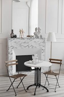 복고풍 테이블, 의자 2 개 및 대리석 벽난로의 흰색 거실 인테리어