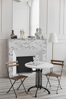 White living room interior of retro table, two chairs, and marble fireplace
