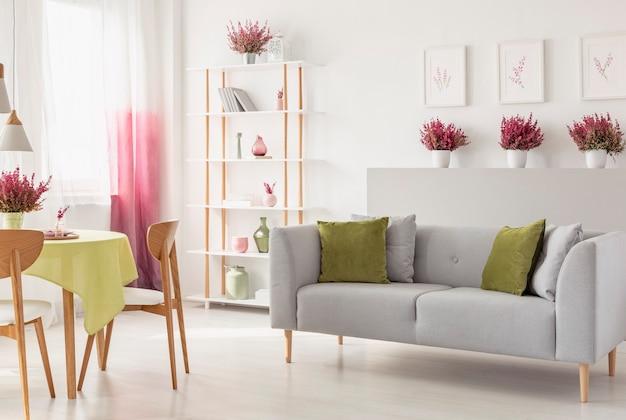 방석이 있는 회색 소파, 꽃병과 책이 있는 선반, 신선한 헤더, 벽에 포스터, 커튼이 있는 창문이 있는 흰색 거실