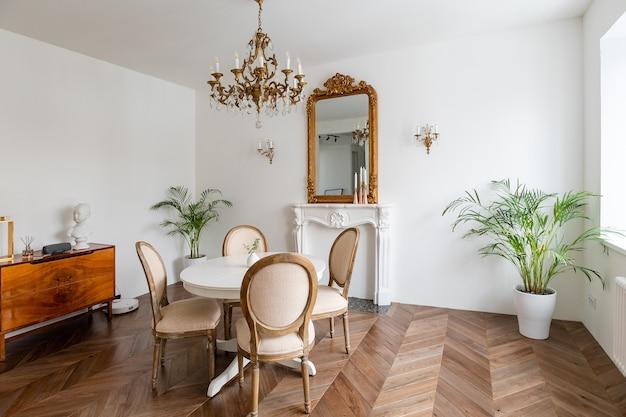고전적인 장식, 거울, 벽난로, 식탁이있는 흰색 거실.