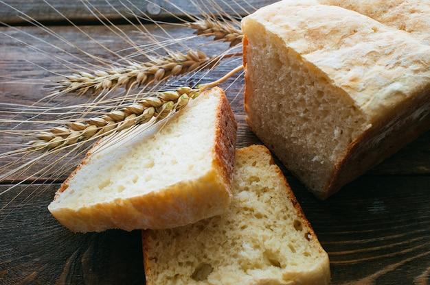 Ломтики белого хлеба и колоски пшеницы на темном деревянном столе