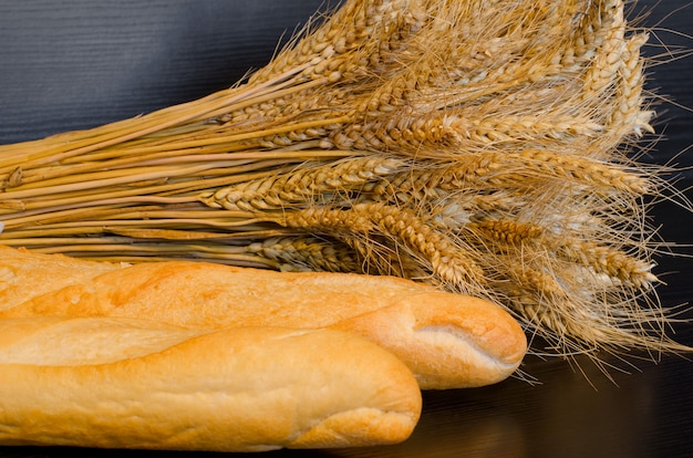 White loaves and a sheaf on a dark surface, close-up