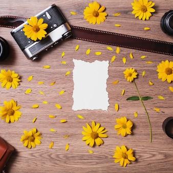 木製のテーブルの上に横たわっている紙の白いロングシート。ビンテージカメラ、レンズ、写真フィルム