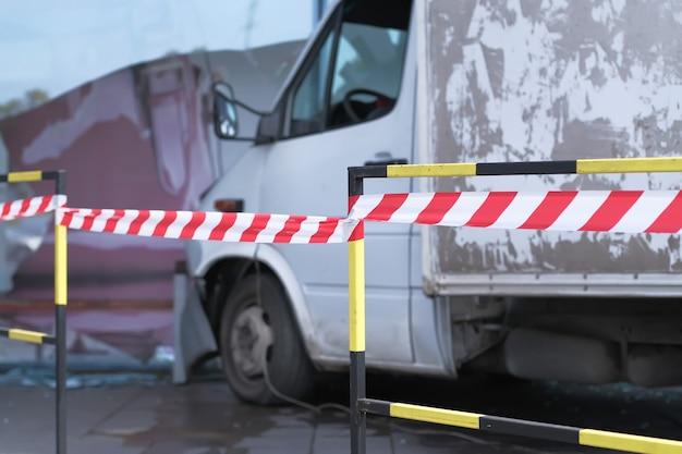 흰색 트럭이 쇼핑몰 유리벽과 충돌했습니다. 도로 사고 현장은 신호 테이프로 격리되고 울타리가 쳐져 있습니다.