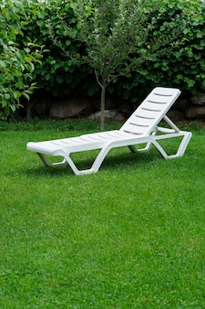 White lounge sunbed standing on green grass in the garden on a summer day. high quality photo