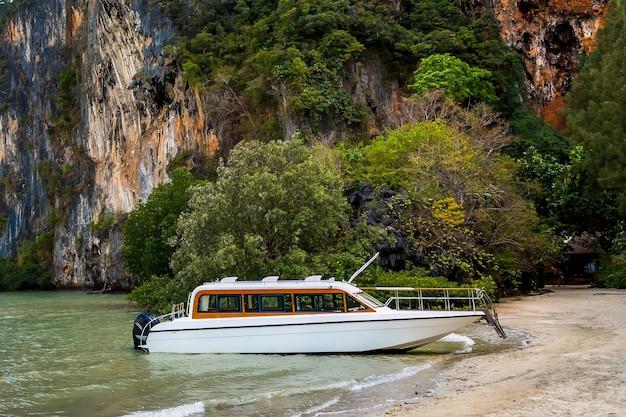 모래에 정박된 열대 섬 해안에서 승객을 기다리는 흰색 럭셔리 모터 스피드보트