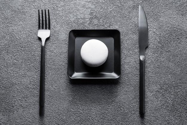 검은 사각형 접시에 흰색 마카로니 케이크. 아름다운 구성, 미니멀리즘, 기하학적 중앙 배열, 테이블 세팅.