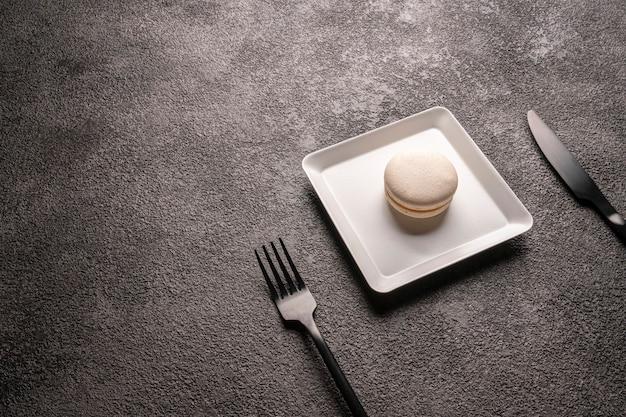 흰색 세련된 접시에 흰색 마카롱 케이크. 최소한의 음식 사진. 다방을위한 디저트. 빈 copyspace 공간.