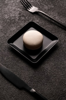 White macaroon cake in a square plate. stylish minimalistic close-up photo. black fork and spoon. graphic food photo in dark colors, vertical arrangement.