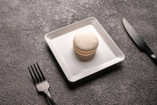 White macaroon cake in a white stylish plate. close-up. dessert for the coffee shop, table setting, black fork and knife
