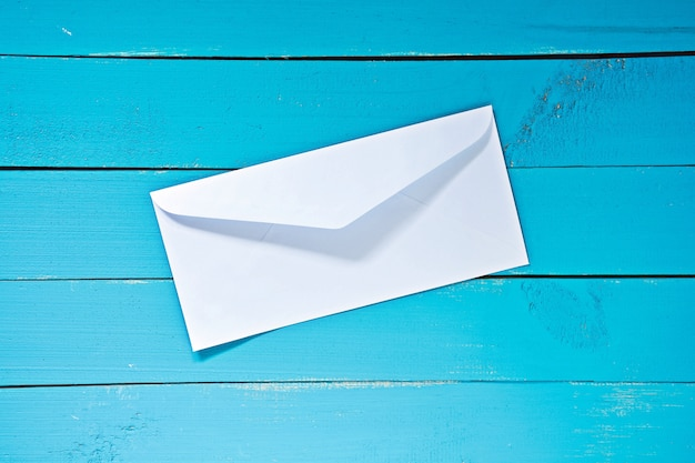 White mail envelope on blue table wood
