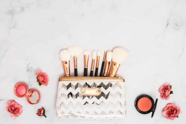 White makeup bag with brushes; compact powder and roses on textured backdrop